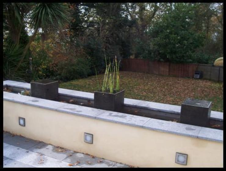 Long water feature with simple planted pots:   by Westacott Gardens