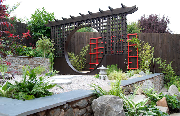 The moon gate with wooden art behind:  Garden by Lush Garden Design