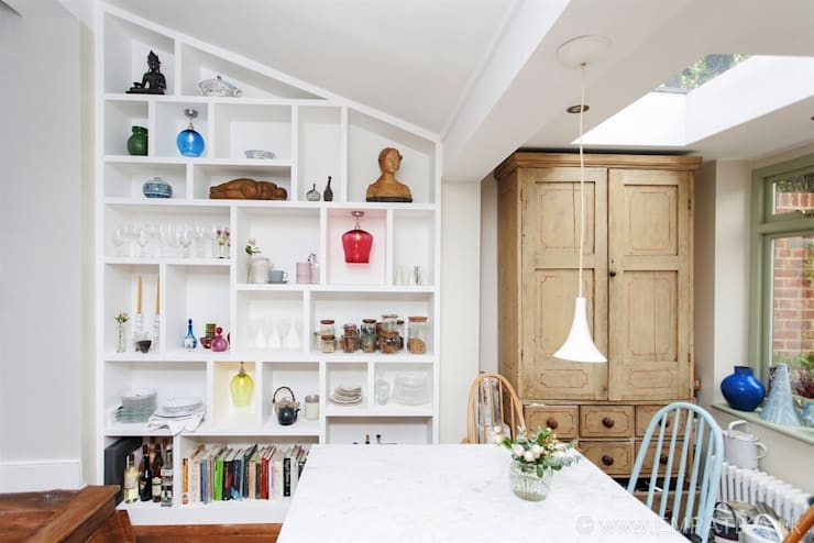 Cosy dining room with custom shelving:  Dining room by Empatika
