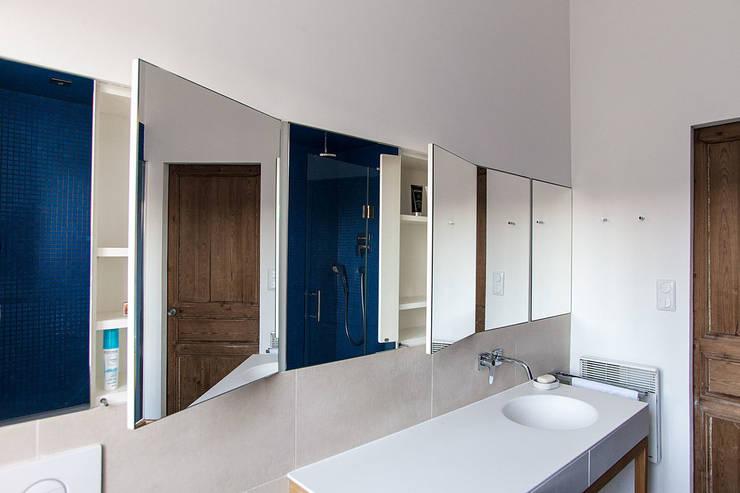 Des rangements se cachent derrière les portes-miroirs: Salle de bain de style de style Moderne par Charlotte Raynaud Studio