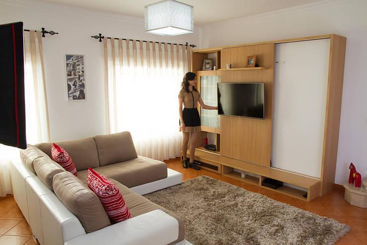 Cama oculta em móvel de sala: Sala de estar  por GenesisDecor