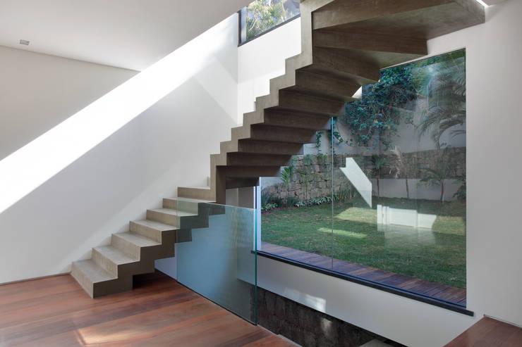Escada em concreto aparente: Corredores e halls de entrada  por House in Rio,