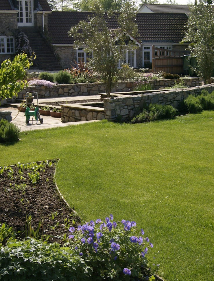 The long, curving wall around the herb beds:   by Christine Wilson Gardens