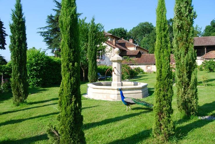 Fontaine centrale en pierre installée dans un jardin: Jardin de style  par Provence Retrouvée