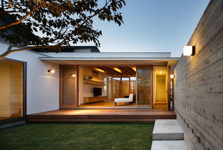 中庭からリビング: 窪江建築設計事務所が手掛けた庭です。