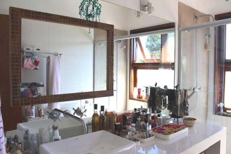 Banho com vista para mata nas janelas superiores.: Banheiros  por Documenta Arquitetura sc ltda