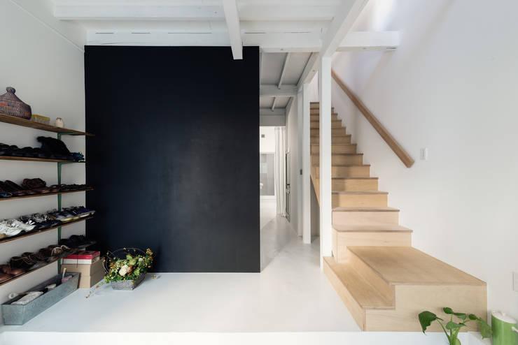 Pasillos y vestíbulos de estilo  por coil松村一輝建設計事務所