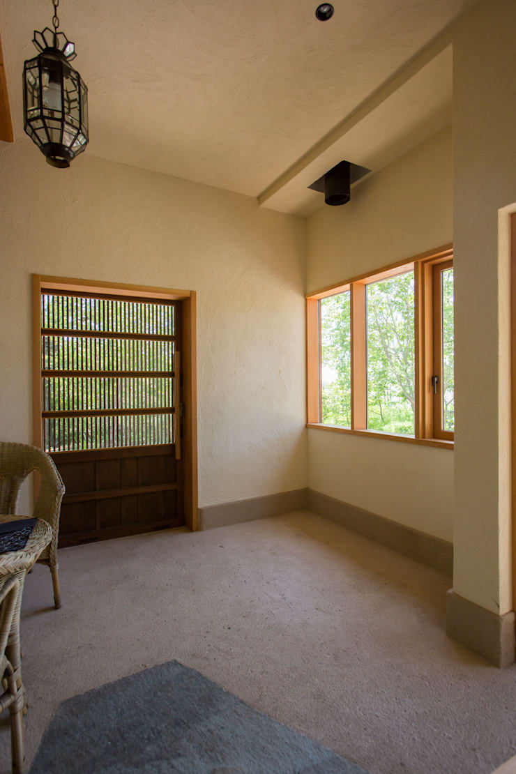 大泉の舎‐土間のある玄関: 有限会社中村建築事務所が手掛けた壁です。,