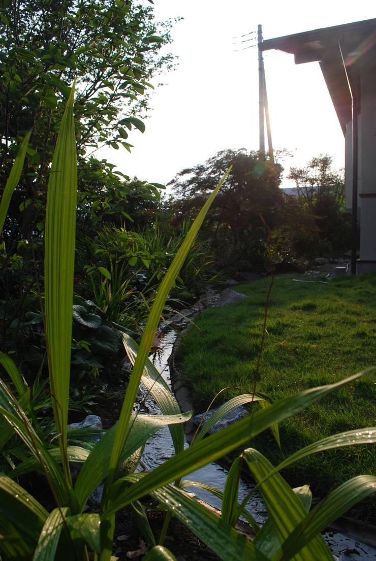 石和の舎‐井戸水の小川が流れる庭: 有限会社中村建築事務所が手掛けた庭です。