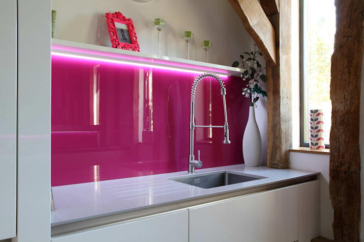 Sleek handle-less kitchen with pink splash-back ensures a modern contemporary look in this barn conversion.:  Kitchen by John Ladbury and Company