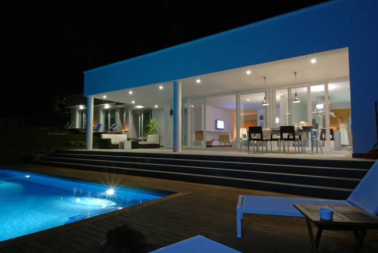 Terraza con jardín y piscina, vista nocturna: Terrazas de estilo  de FG ARQUITECTES