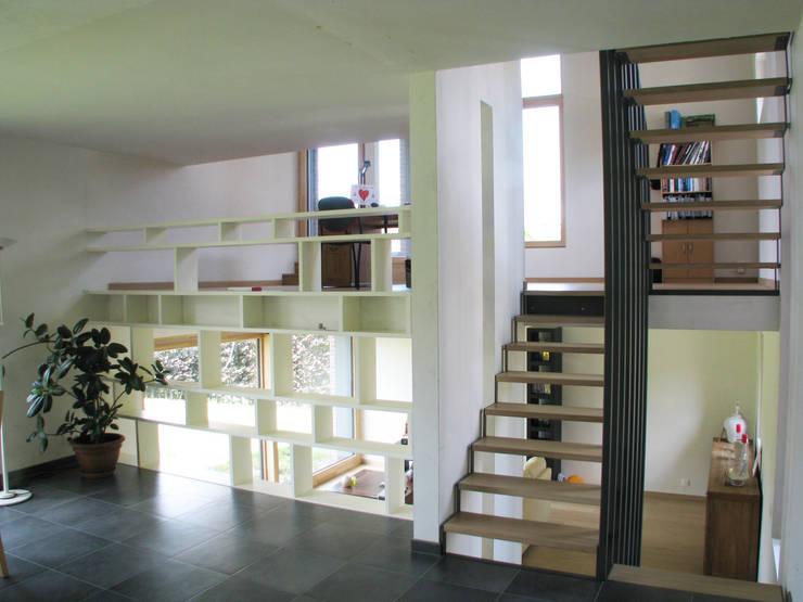 Escalier à claire-voie et bibliothèque délimitent en offrant des contacts visuels.: Salon de style de style Minimaliste par dune Architecture sprl