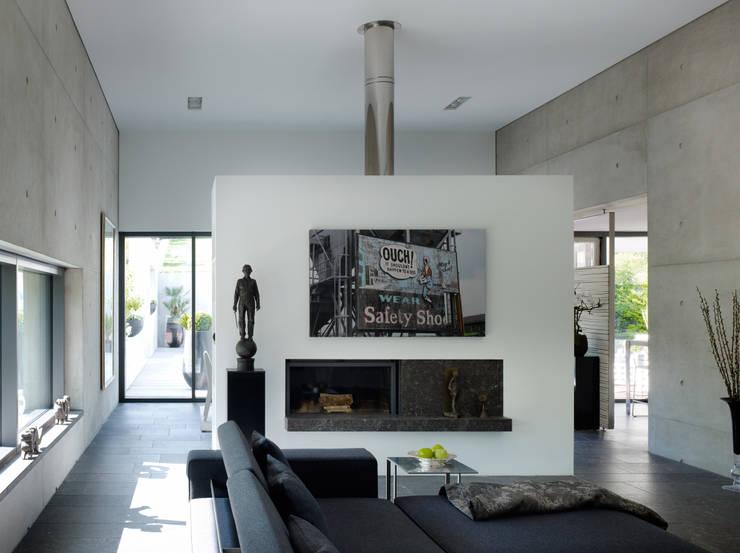 Wohnraum  mit Kamin: minimalistische Wohnzimmer von PaulBretz Architectes