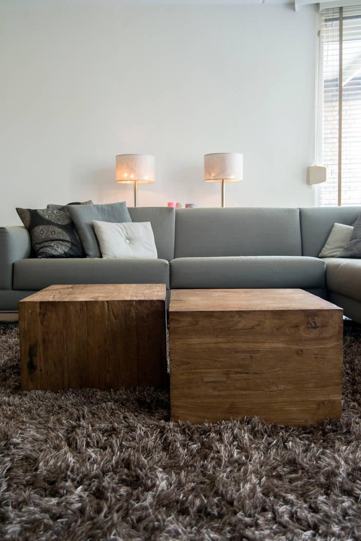 Moderne bank in combinatie met grove houten salontafels:  Woonkamer door Hemels Wonen interieuradvies en ontwerp