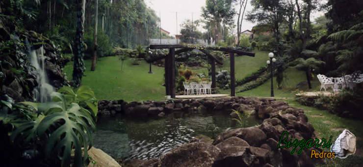 Pergolado com o paisagismo em volta: Jardins  por Bizzarri Pedras