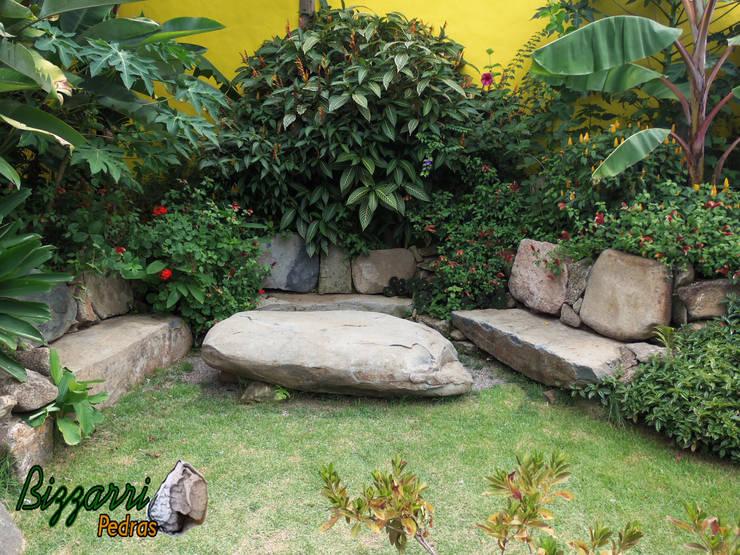 Banco com pedra moledo: Jardins rústicos por Bizzarri Pedras