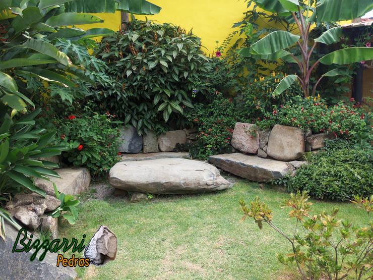 Banco com pedra moledo: Jardins  por Bizzarri Pedras