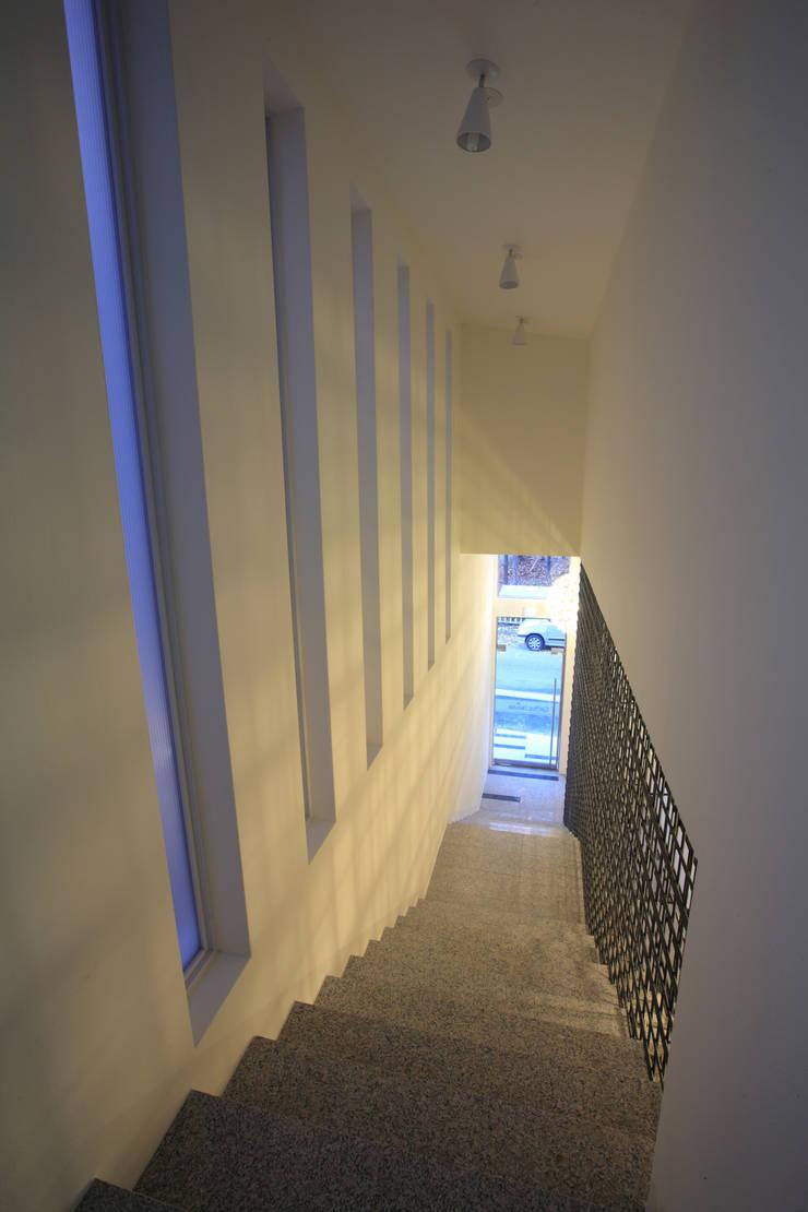 1층 계단실: 현앤전 건축사 사무소(HYUN AND JEON ARCHITECTURAL OFFICE )의  복도 & 현관