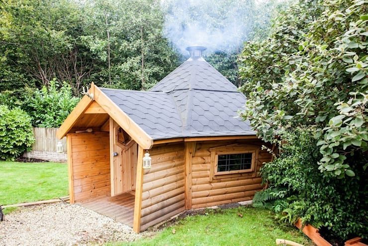A 10m² barbecue cabin with a short porch extension. Fire going well inside by the looks of it. :  Garden by Arctic Cabins