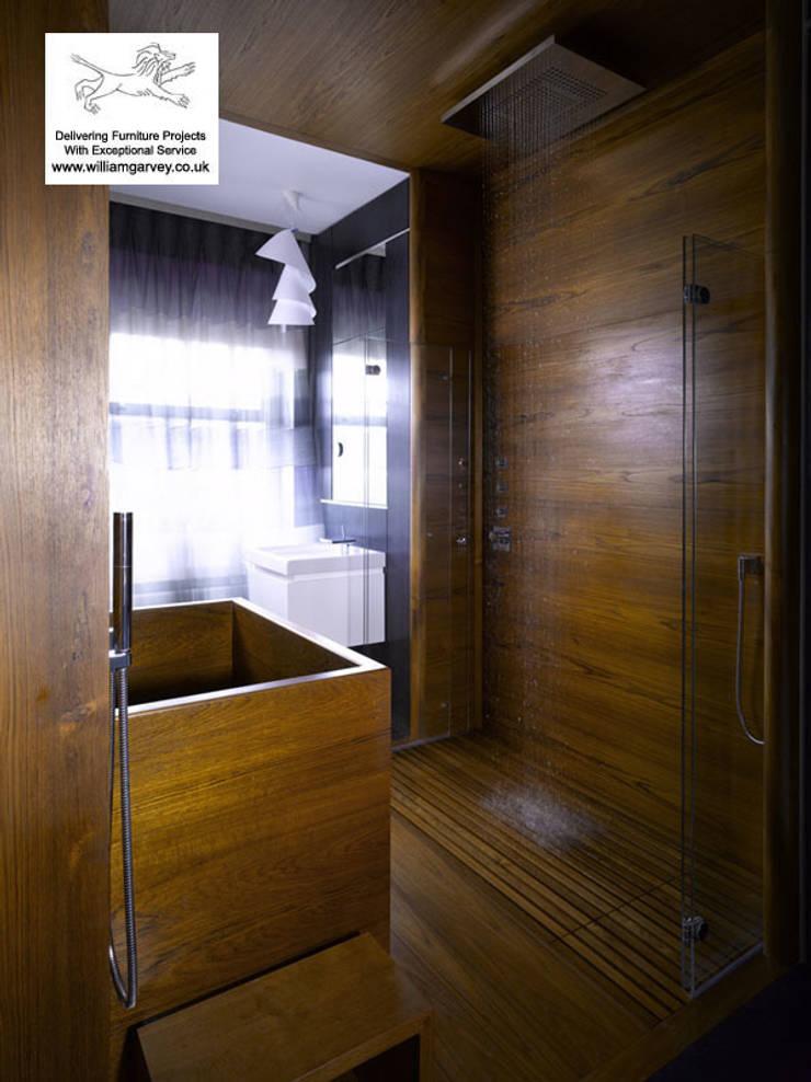 Teak bath, wall tiles and duckboard:  Bathroom by William Garvey Ltd