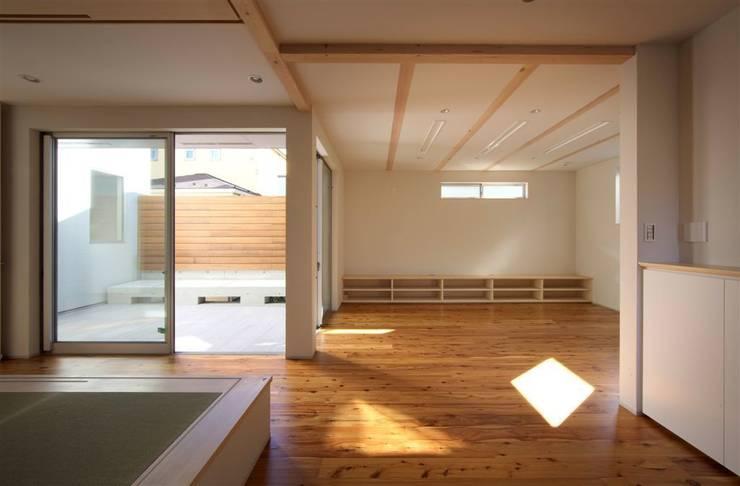 趣味の地下空間をもつコートハウス: 充総合計画 一級建築士事務所が手掛けたリビングです。