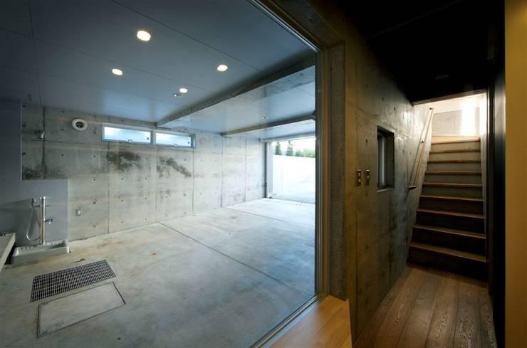 趣味の地下空間をもつコートハウス: 充総合計画 一級建築士事務所が手掛けたガレージです。