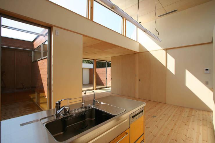 愛車を眺める住まい: STUDIO POHが手掛けたキッチンです。