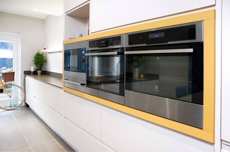 Electrolux appliances wrapped in Curry Yellow panelling: modern Kitchen by Haus12 Interiors