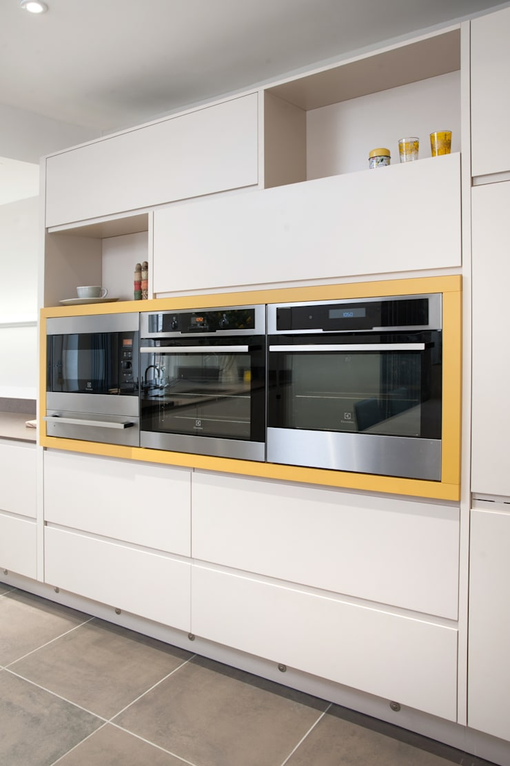 Electrolux appliances wrapped in Curry Yellow panelling:  Kitchen by Haus12 Interiors