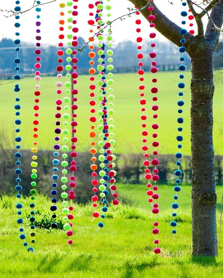 Pom Pom Garlands hanging in tree Eclectic style garden by PomPom Galore Eclectic