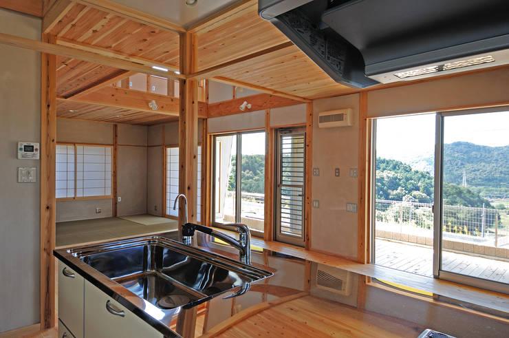家の中心に位置するキッチンよりの眺め: 氏原求建築設計工房が手掛けたキッチンです。
