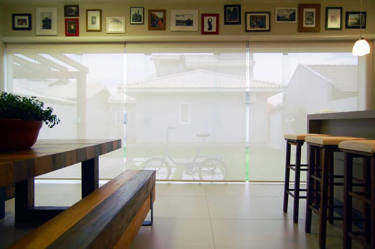 Área de lazer com espaço para refeições, cozinha e pub particular: Salas de jantar  por Sandro Clemes