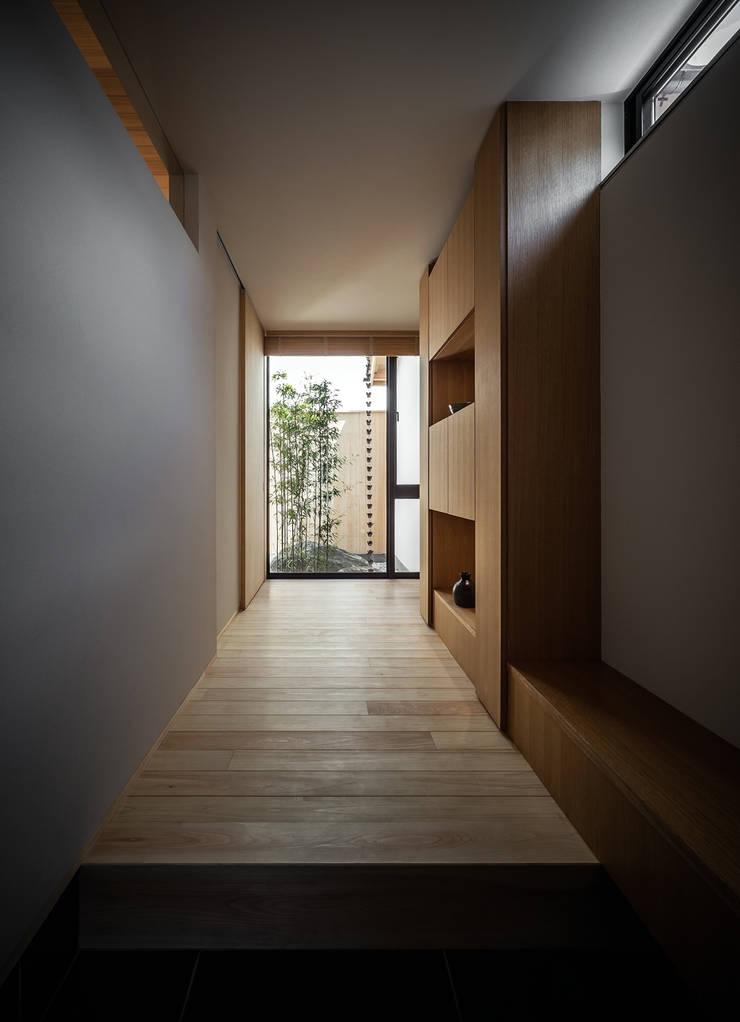 それぞれの庭の家 玄関から[黒竹と苔むす岩の庭]をのぞむ: 株式会社seki.designが手掛けた廊下 & 玄関です。