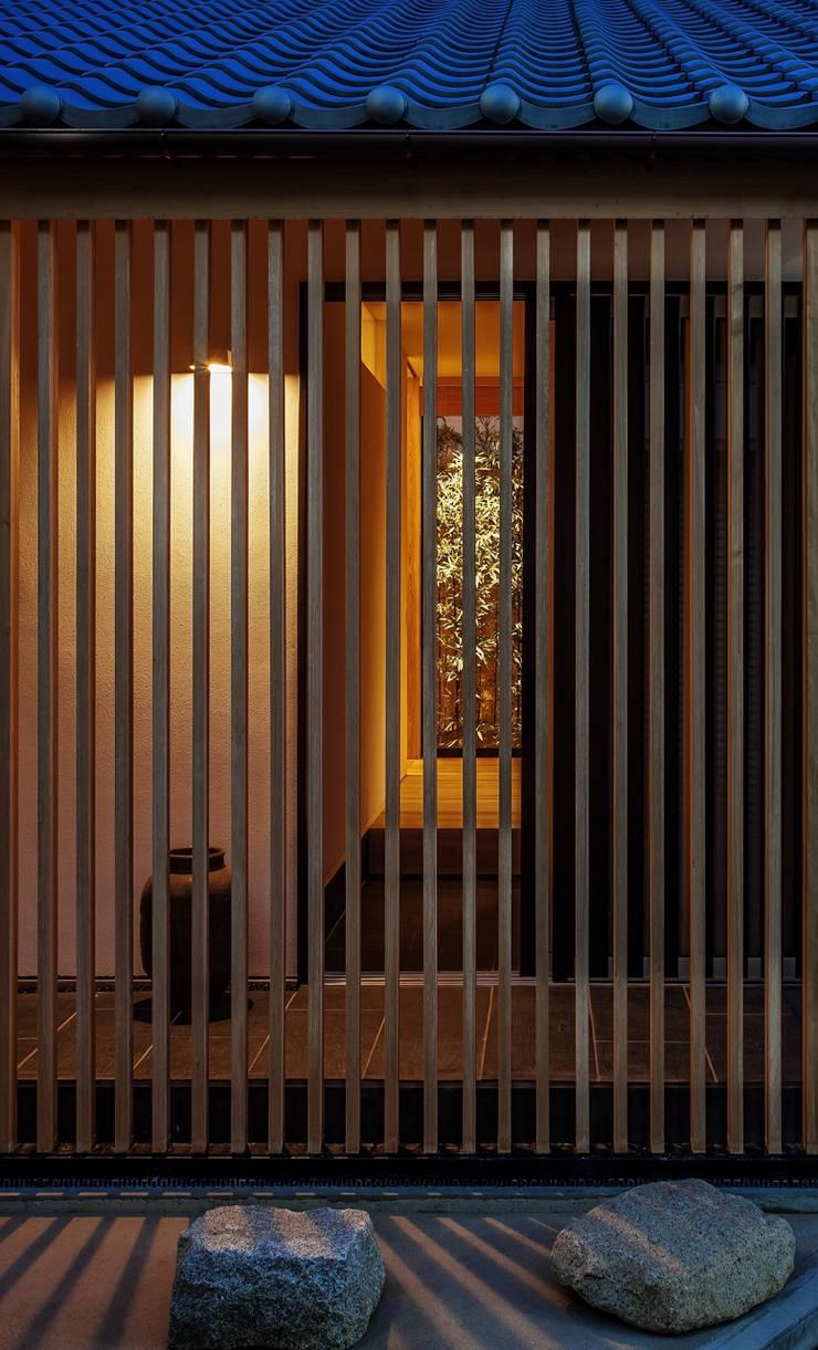 それぞれの庭の家 縦格子越しに玄関、[黒竹と苔むす岩]を見通す: 株式会社seki.designが手掛けた家です。