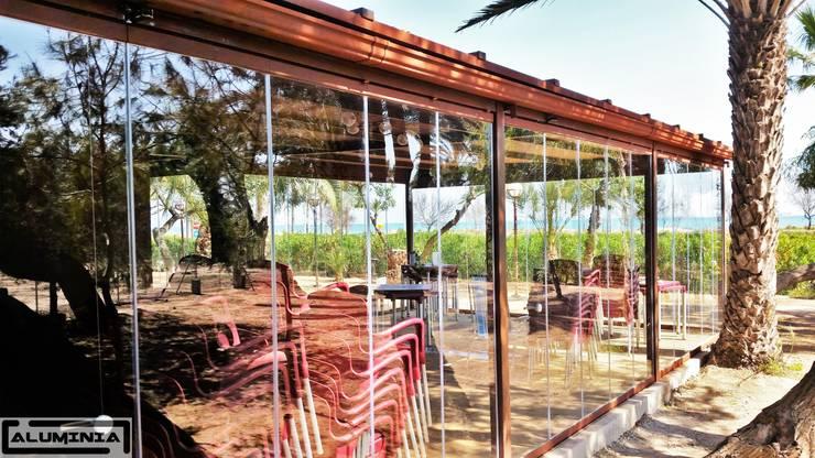 Cerramiento cortina de cristal en restaurante la goleta: Terrazas de estilo  de Aluminia Sistemas y Accesorios S.L.