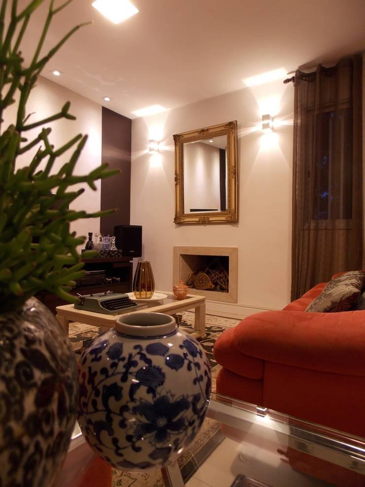 Sala aconchegante com sofás vermelhos: Salas de estar  por Lúcia Vale Interiores,