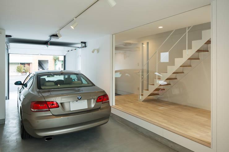 ガレージ越しに玄関と階段を見る。: 田中幸実建築アトリエが手掛けた壁&床です。
