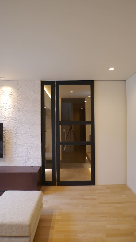 エントランスとリビングルームを結ぶ扉: 株式会社スター・ウェッジが手掛けた窓です。