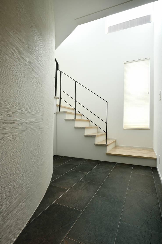 白と黒のコントラストが美しいエントランスホール: 株式会社スター・ウェッジが手掛けた壁です。