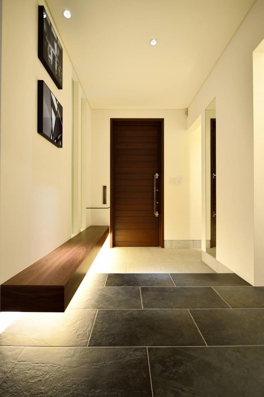 柔らかな灯りに迎えられるエントランス: 株式会社スター・ウェッジが手掛けた壁&床です。