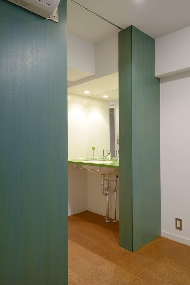 グリーンの壁: ティー・ケー・ワークショップ一級建築士事務所が手掛けた浴室です。