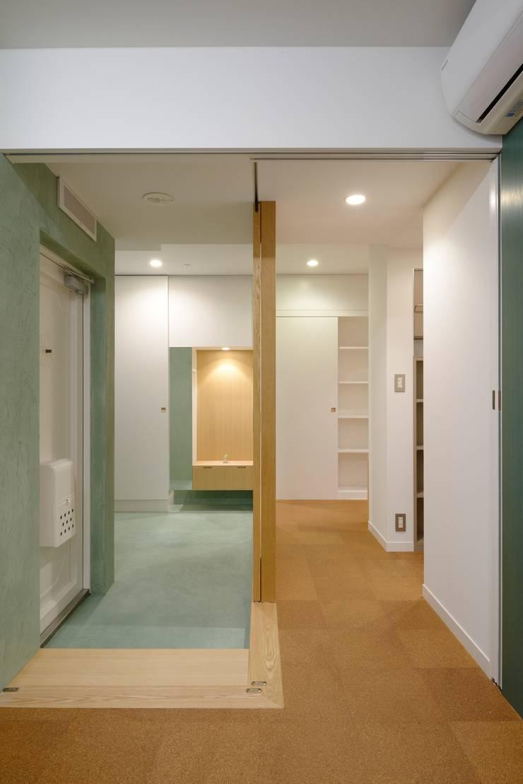玄関と通路: ティー・ケー・ワークショップ一級建築士事務所が手掛けた壁&床です。