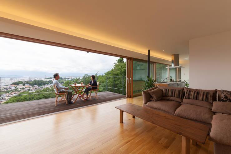 善光寺平を望む家: 伊東亮一建築設計事務所が手掛けたリビングです。
