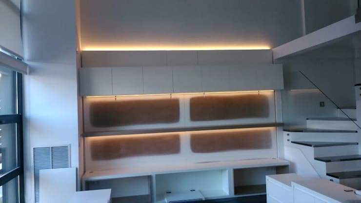 Zona trasera de mesas de despachos diseñadas con todo el entorno, con luz led indirecta y regulables.: Estudio de estilo  de key home designers