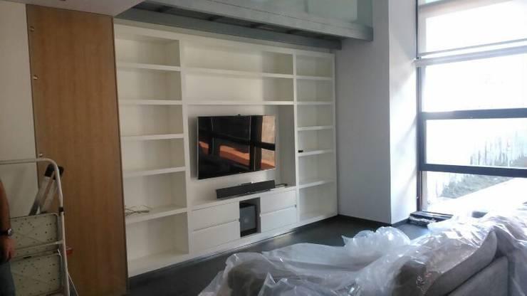 Parte de abajo de la libreria de 5 mts,  lleva la Tv totalmente oculta con unas puertas especiales con roble y espejo perlado correderas.: Estudios y despachos de estilo  de key home designers