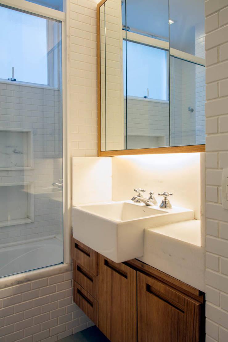 APARTAMENTO KG: Banheiros  por Raquel Junqueira Arquitetura