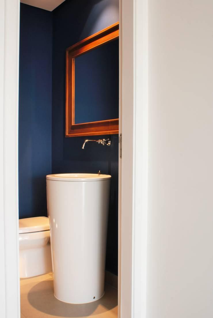 Lavabo com paredes azuis : Banheiros  por Gisele Emery Arquitetura,