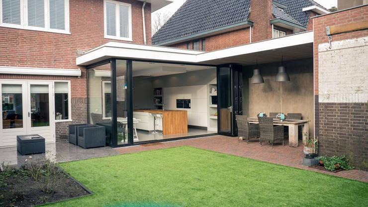 Aanbouw en renovatie van 2-onder-1-kapper met ruime woonkeuken met kookeiland, gietvloer en luxe aluminium vouwschuifpui:  Terras door Joep van Os Architectenbureau