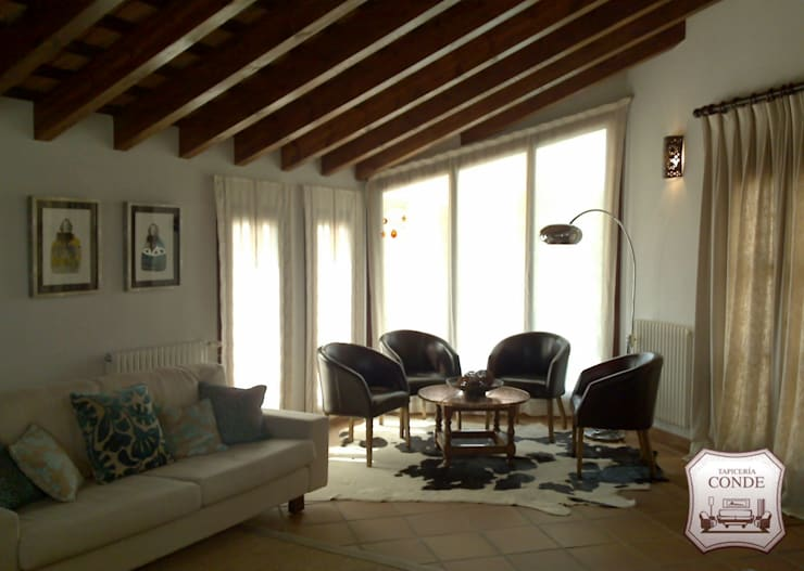 Decoración de salón. Tapizado de sofás y  sillones, Confección de cortinas, estores, alfombra.: Salones de estilo  de Tapicería Conde