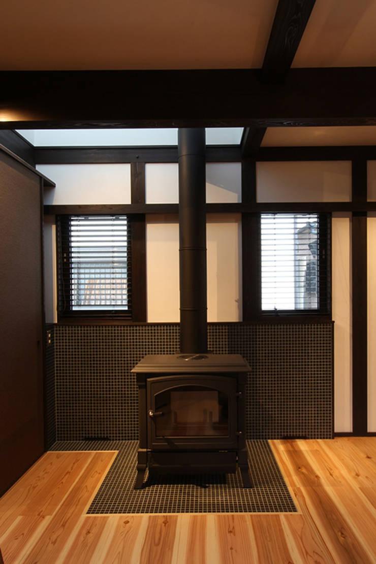 薪ストーブと小さな吹抜け: 安井正/クラフトサイエンスが手掛けたリビングルームです。